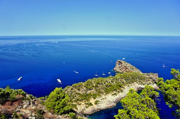 Krajobraz sa foradada majorka, hiszpania z klifów. łodzie dostrzegają błękitne morze.
