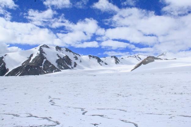 Krajobraz skał pokrytych śniegiem w słońcu i pochmurnym niebie