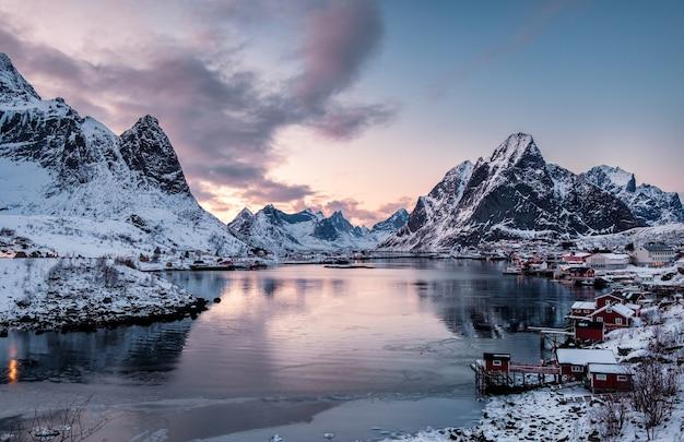 Krajobraz skandynawskiej miejscowości w dolinie na wybrzeżu o zachodzie słońca, reine, lofoty, norwegia
