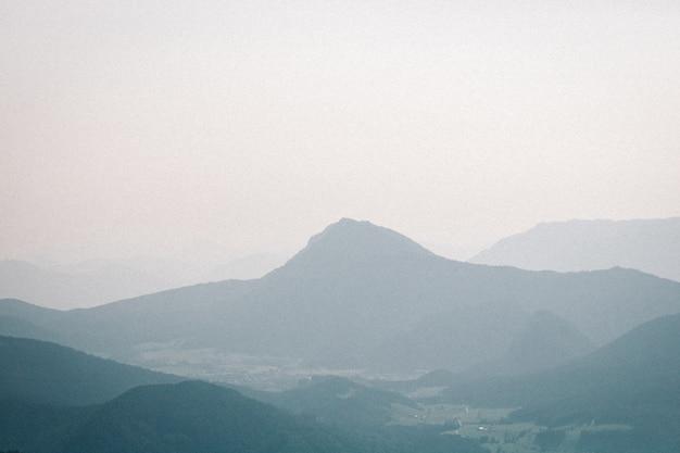 Krajobraz strzał mglistej góry z ponurym niebem w tle