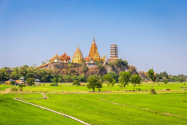 Krajobraz świątyni wat tham sua (świątynia tygrysia jaskinia) z jaśminowymi polami ryżowymi