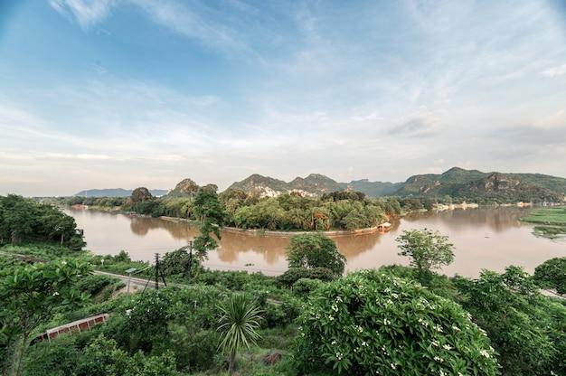 Krajobraz tropikalnych lasów deszczowych i historycznej linii kolejowej na rzece kwai wieczorem w kanchanaburi, tajlandia. punkt widokowy wat tham khao pun