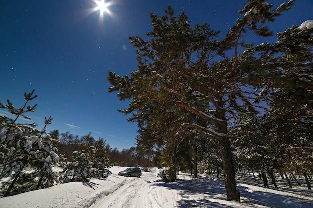 Krajobraz utknął w samochodzie turystycznym w głębokim śniegu. sfotografowany w zimową noc przy pełni księżyca.