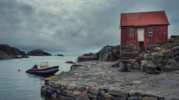 Krajobraz w norwegii. samotność z naturą. tradycyjna samotna czerwona drewniana chatka na skalistym brzegu północnego morza i łódź w zatoce.