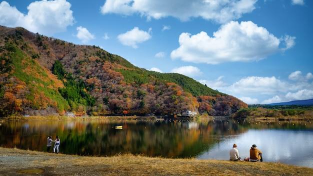 Krajobraz widok jesiennych liści jeziora kawaguchiko i para siedzi nad rzeką w japonii
