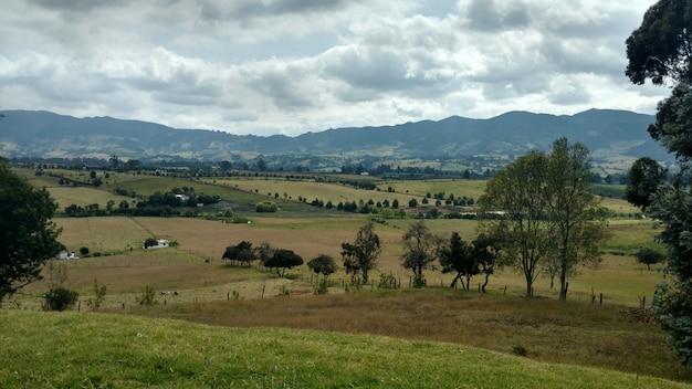 Krajobraz wiejskiego obszaru otoczonego wzgórzami pokrytymi zielenią pod zachmurzonym niebem w ciągu dnia