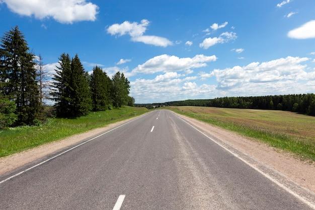 Krajobraz wiosną. droga asfaltowa, las i błękitne niebo