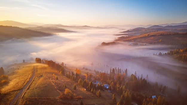 Krajobraz wschód słońca nad górską mglistą doliną