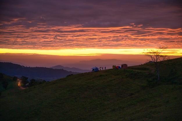 Krajobraz wschodu słońca nad górą z namiotem na wzgórzu na wsi o poranku