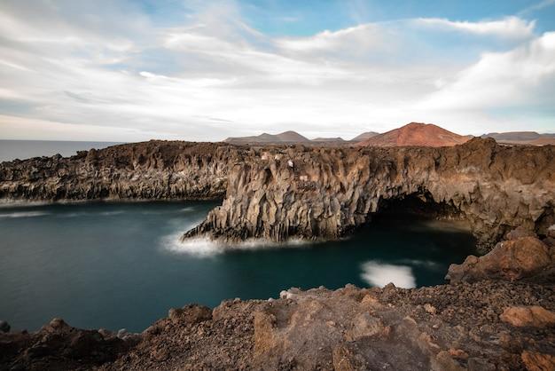 Krajobraz wulkanicznego wybrzeża los hervideros z morskimi jaskiniami, w których załamują się fale.