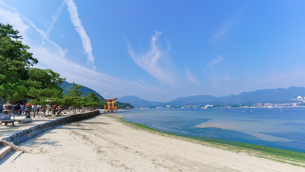 Krajobraz wybrzeża morskiego na wyspie miyajima z widokiem na słynną pomarańczową pływającą japońską bramę shinto (torii) świątyni itsukushima w zatoce
