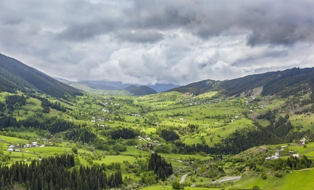 Krajobraz wzgórz pokrytych budynkami i lasami pod ciemnym zachmurzonym niebem