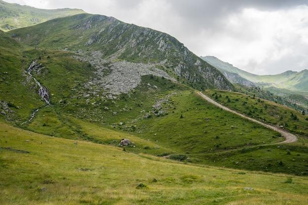 Krajobraz wzgórz pokrytych zielenią pod błękitnym niebem i słońcem w ciągu dnia