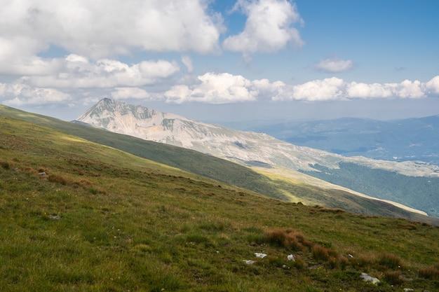 Krajobraz wzgórz pokrytych zielenią z górami pod zachmurzonym niebem