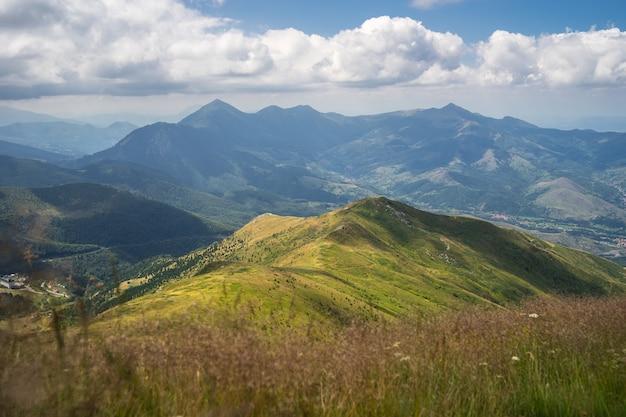Krajobraz wzgórz pokrytych zielenią z górami skalistymi pod zachmurzonym niebem na