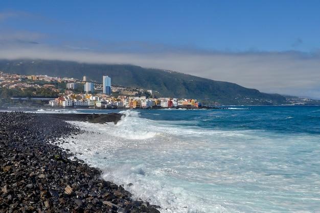 Krajobraz z czarnym wulkanicznym piaskiem i dużymi falami