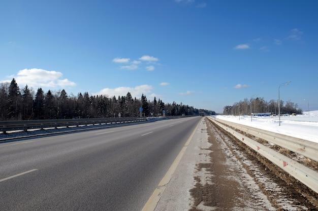 Krajobraz z długą prostą podmiejską autostradą z metalowym ogrodzeniem po bokach i lasem pod błękitnym niebem w jasny słoneczny zimowy dzień