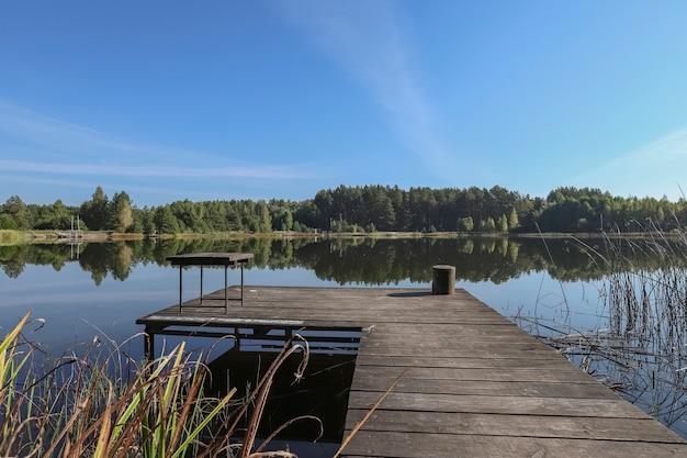 Krajobraz z drewnianym długim pomostem z krzesłem do łowienia w lesie nad jeziorem na horyzoncie i błękitnym niebem w...