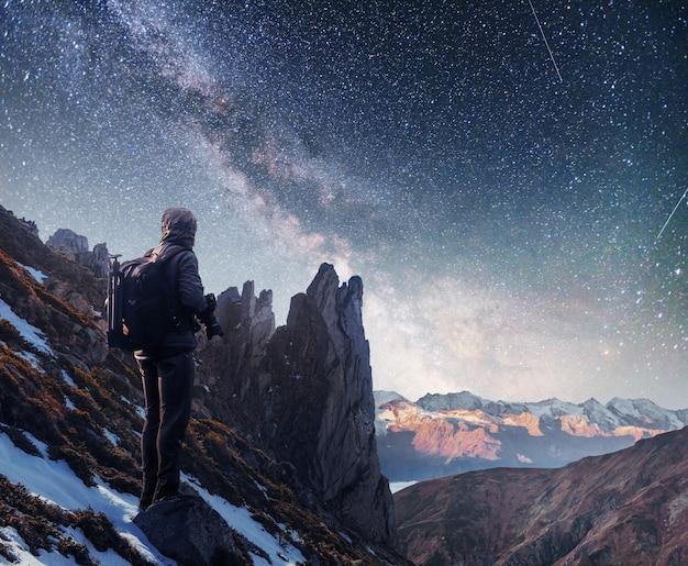 Krajobraz z drogą mleczną, gwiazdami nocnego nieba i sylwetką stojącego fotografa mężczyzny na górze.