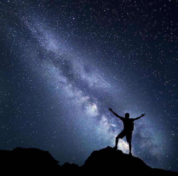 Krajobraz z drogą mleczną. nocne niebo z gwiazdami i sylwetka szczęśliwego wspinacza z plecakiem i wzniesionymi rękami na górze.