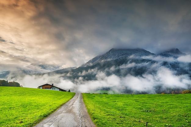 Krajobraz z drogą, zielonym polem i górami w chmurach