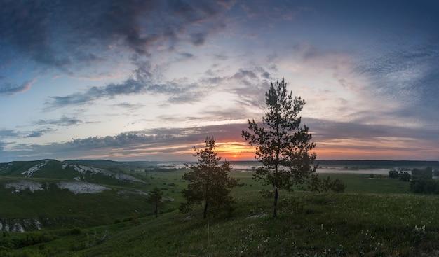 Krajobraz z drzewami na wzgórzu i wschodzie słońca, majestatyczne chmury na niebie