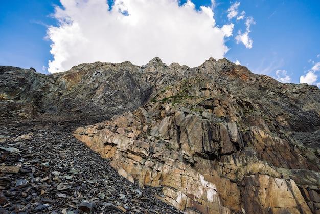 Krajobraz z gigantyczną białą chmurą nad wielką skalistą górą w kolorach ziemi