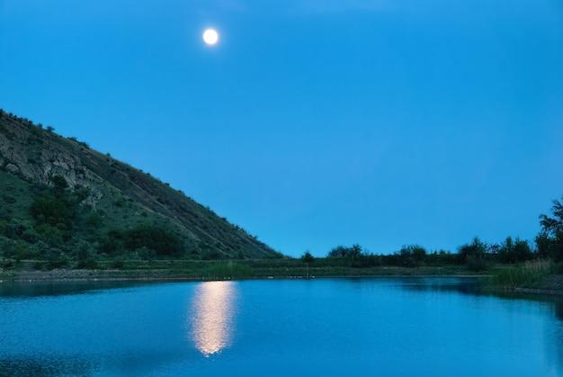 Krajobraz z księżycem nad jeziorem. ciemnoniebieska noc i odbicie światła księżyca w wodzie