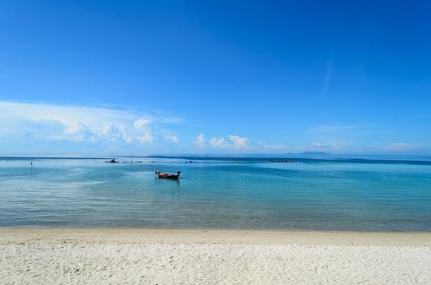 Krajobraz z łodzią i morzem pod niebieskim niebem w ranku
