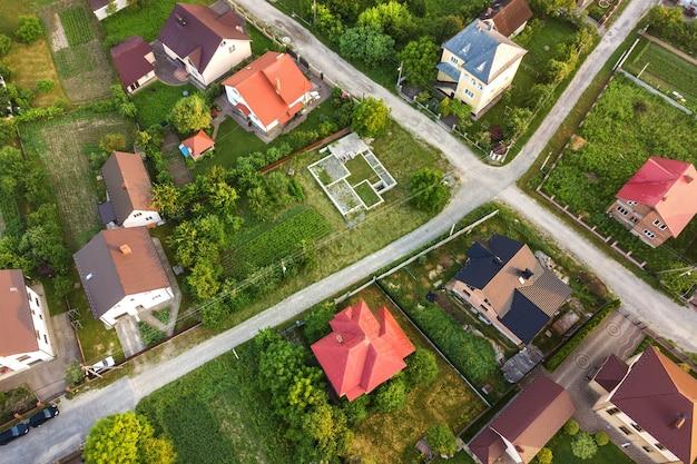 Krajobraz z lotu ptaka małego miasteczka lub wioski z rzędami domów mieszkalnych i zielonymi drzewami.