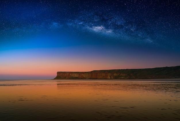 Krajobraz z milky sposobu galaxy nad falezą przy saltburn morzem, north yorkshire, uk