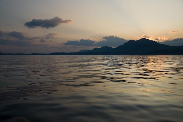 Krajobraz z morzem i górami na zachodzie słońca