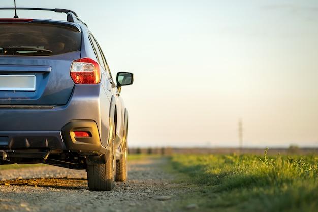 Krajobraz z niebieskim off road samochód na żwirowej drodze. podróż samochodem, przygoda z dziką przyrodą, wyprawa lub ekstremalna podróż samochodem typu suv. pojazd terenowy 4x4 w polu o wschodzie słońca.