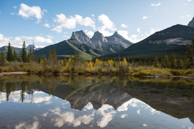 Krajobraz z odbiciem góry trzech sióstr nad bow river w jesiennym lesie w canmore, ab, kanada