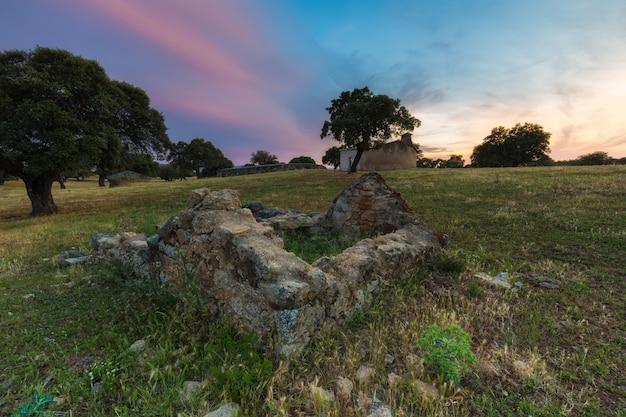 Krajobraz z ruinami o zachodzie słońca.