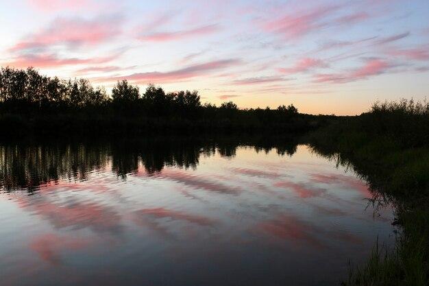 Krajobraz z widokiem na różowe chmury nad jeziorem o zachodzie słońca