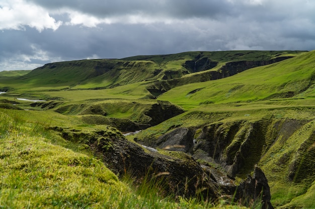 Krajobraz z zieloną trawą, chmurami i odległym wodospadem