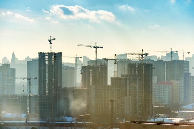Krajobraz zachód słońca w mieście z błękitnym niebem, słońcem i żurawiami przemysłowymi