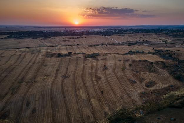 Krajobraz zachodzącego słońca z miastem malpartida de caceres w tle.