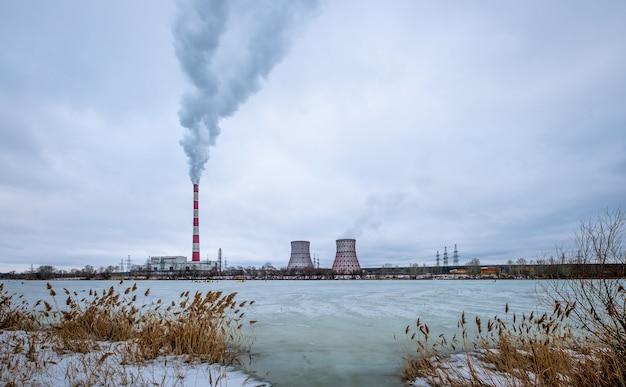 Krajobraz ze stacją cieplną i dymem z dużych rur przemysłowych