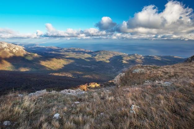 Krajobraz ze szczytu górskiego i majestatycznych chmur na niebie, z morzem