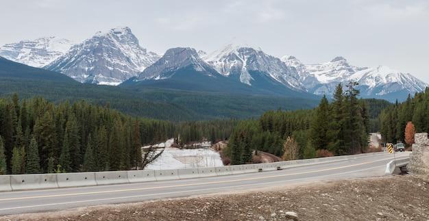 Krajobraz zimowy widok krzywej nicholas morants na canadian pacific railway i bow river na tle gór skalistych trzech sióstr