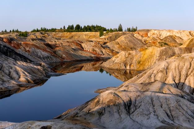 Krajobrazowe jezioro na dnie dawnego kamieniołomu wydobycia kaolinu z pięknymi zboczami
