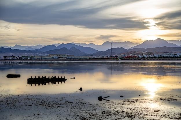 Krajobrazowe niebo odbija się w morzu w zachodzącym świetle. wybrzeże miasta z górami na horyzoncie.