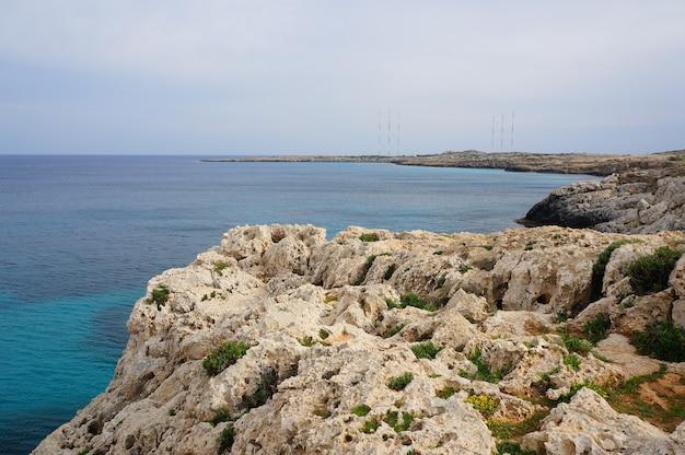 Krajobrazowy widok na skalistym brzegu oceanu pod błękitnym niebem