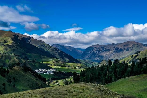 Krajobrazowy widok na zielone góry i drzewa pod błękitnym niebem