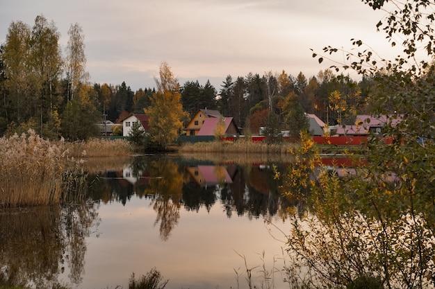 Krajobrazowy widok wiejskich domów na brzegu stawu, odbijając się w wodzie o zachodzie słońca