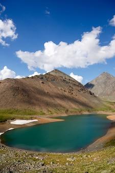 Krajobrazy ałtaju. mountain spirit lake. niebo i puszyste chmury, jezioro z turkusową wodą pośrodku wysokich klifów