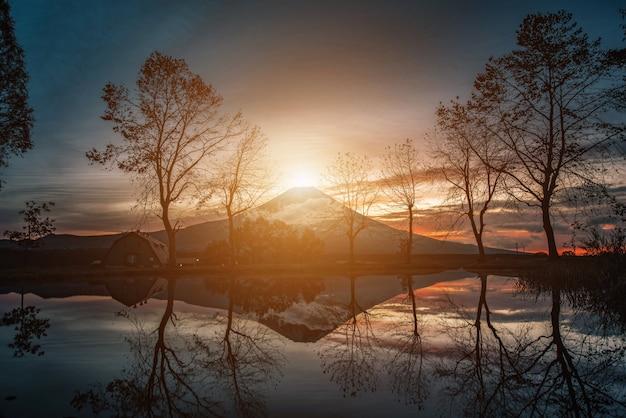 Krajobrazy fuji mountian z dużymi drzewami i jeziorem o wschodzie słońca w fumotopara camp, fujinomiya, japonia.