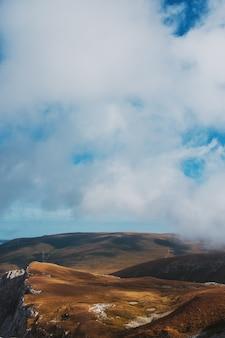Krajobrazy z niebieskim niebem i chmurami, trasa przez szczyty górskie i wzgórza przez majestatyczny